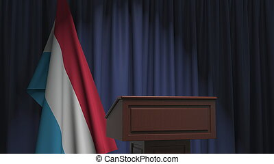 National flag of Luxembourg and speaker podium tribune. ...