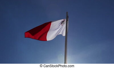 National flag of Malta on a flagpole in front of blue sky