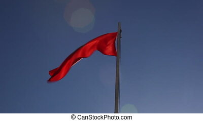 National flag of Morocco on a flagpole in front of blue sky