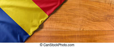 National flag of Romania on a wooden background with copy space