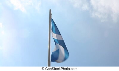 National flag of Scotland on a flagpole in front of blue sky