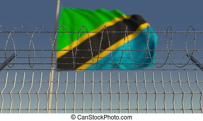 National flag of Tanzania behind barbed wire fence....