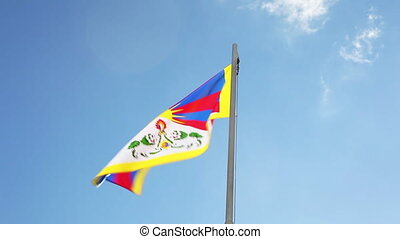 National flag of Tibet on a flagpole in front of blue sky