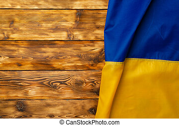 National flag of Ukraine on dark wooden background