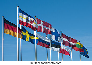 The National flags of the states around the baltic sea, Europe, and the common flag of the European Union flying in the wind behind blue sky.