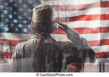National holidays in the United States. A female soldier saluting, against the background of the American flag. Rear view. Double exposure