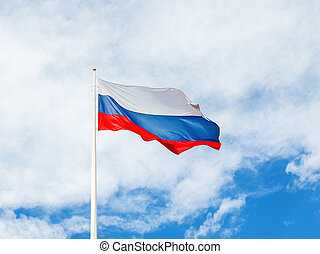 National Russian flag waving on cloudy blue sky background.