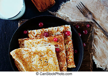 National Russian food. Pancakes in a frying pan with milk. Rustic stylization