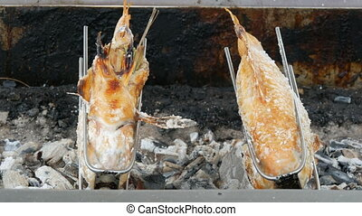 National Thai dish, fried fish on spit in salt and with greens. Exotic food of Thailand and Asia