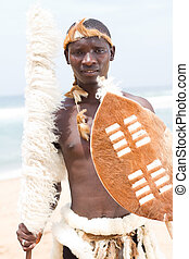 native african man with traditional clothing on beach