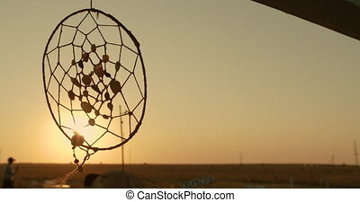 Native American dreamcatcher hanging in breeze at sunset. - ...