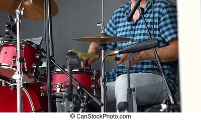 A close up and slow motion clip of a musician playing a modern drum kit with traditional indigenous natural beaters during a local music concert, with copy-space.