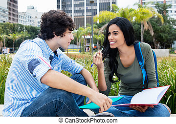 Native latin american student talking with friend outdoors...