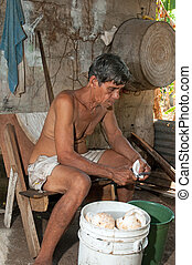 native senior man cleaning slicing fresh coconut for...