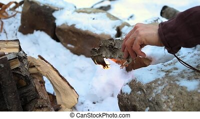 Close up footage on the hand of a native tribe man lighting a camp fire with wood logs and sticks in winter as heavy snow lies on ground, with copy space