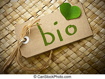 Natual cardboard label with the word bio hanwritten on it plus a green clover petal