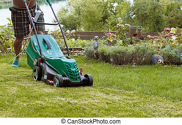 Natural background A man mows a lawn mower with a green lawn in his own garden near a flower garden in summer. Side view, horizontal. The concept of design, nature and landscaping.