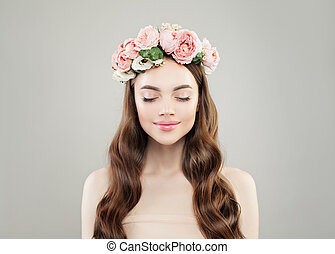 Natural beauty. Pretty woman enjoying. Model girl with clear skin, long brown curly hair and flowers