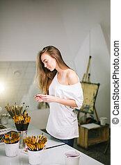 Natural beauty teacher painter in her studio preparing to an art class