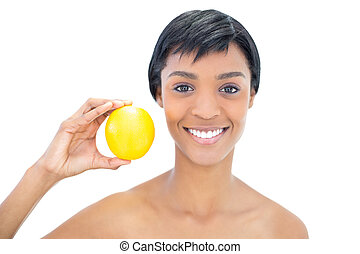 Natural black haired woman holding an orange