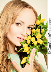 Natural Blond Beauty. Woman with Yellow Tulip Flowers