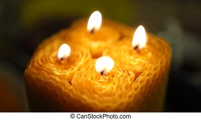 Natural candles made of beeswax in the interior. Woman lights decorative wax candle, close-up of hands. A lighted candle. Handmade. DIY wax candle. Selective focus. Celebration concept.