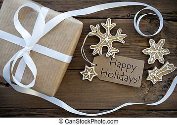 Natural Looking brown Gift with white Ribbon and Ginger Bread Cookies with white Decoration with a brown Label on which stands Happy Holidays, Wooden Background