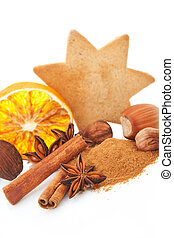 Natural christmas still life with cinnamon, various nuts, gingerbread cookie and orange on white background.