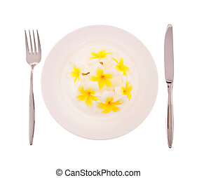 Natural concept, flowers on white plate with fork and knife ...