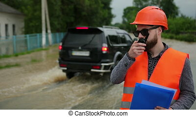Natural disaster major flooding underwater entire community and neighborhood flooded. Homes, houses overflowing with water, home insurance needed. Engineer on the walkie talkie using
