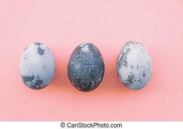 Natural dyed gray colored eggs on pastel pink background.