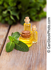 Natural essential oil in a glass bottles with mint leaves