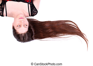 Woman without makeup looking natural while laying down with long brown hair to the side on a white background