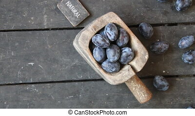 natural food idea, plums on old rural background and text -...