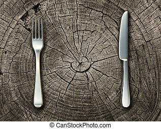 Natural food concept and organic eating healthy lifestyle idea with a silver fork and knife on a cut tree stump log representing raw food and rustic country cooking and traditional cuisine.