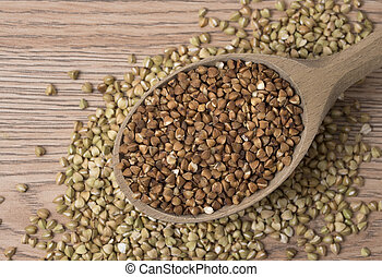 Natural fresh buckwheat in wooden spoon. On a wooden table.