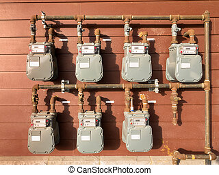 Natural gas meter bank on outside building wall - Bank of...