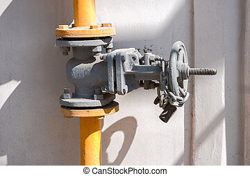 Natural gas valve on steel pipe painted in yellow with shadows