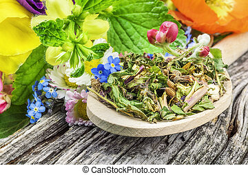 Natural herbal tea on wooden spoon with meadow flowers