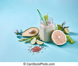 Natural ingredients for healthy smoothie from avocado with cucumber, celery, shpinach, lemon, flax seeds in glass jar on green.
