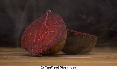 Natural juicy beets on a black background in the smoke,...