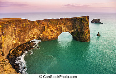 Natural lava arch in the sea. Cape Dyrholaey, coast of Iceland.