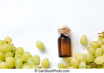 natural organic grape seed oil in a glass bottle on white background .