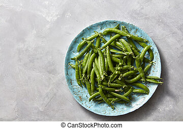Natural organic green peas in sticks on a blue ceramic plate on a gray marble kitchen table. Top view.