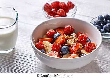 Natural organic raspberry, strawberry, blueberry, nuts, oat flakes and soy milk - the set of ingredients for healthy breakfast on a wooden background