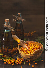 Natural, organic sea-buckthorn berry in bowl and sea buckthorn oil in glass vintage bottle on dark wooden background