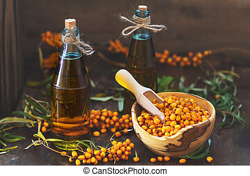 Natural, organic sea-buckthorn berry in bowl and sea buckthorn oil in glass vintage bottle