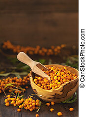 Natural, organic sea buckthorn berry in bowl on dark wooden...