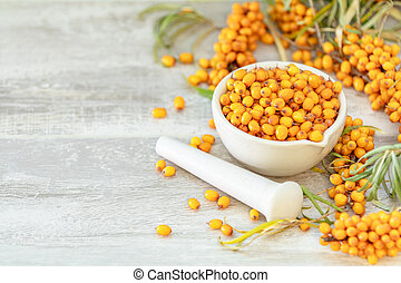 Natural, organic sea-buckthorn berry in white ceramic mortar.