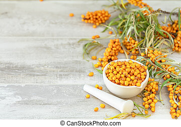 Natural, organic sea-buckthorn berry in white ceramic mortar